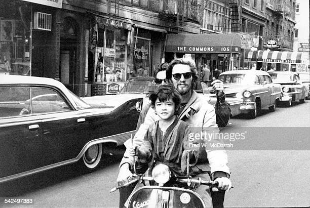 View of poet and cafe owner Ron von Ehmsen drives a Vespa scooter with two unidentified passengers on Macdougal Street New York New York October 16...