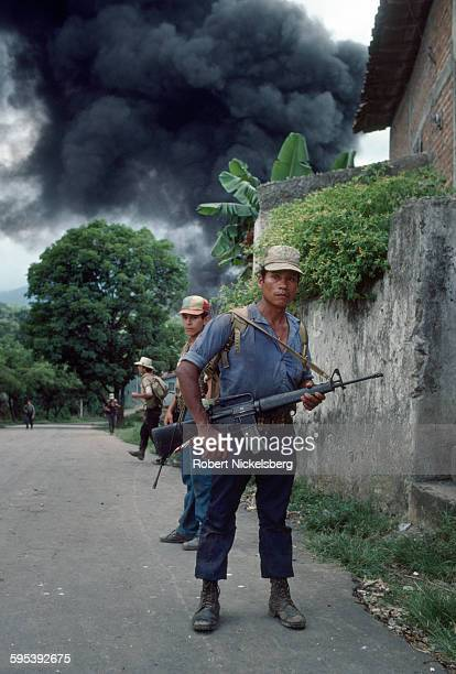View of Popular Revolutionary Forces guerrillas on a street as in the distance black smoke rises during combat San Miguel El Salvador September 1...
