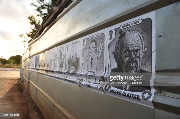 A view of posters on a wall showing caricatures of various football related celebrities including Ricardo Texeira Ronaldo Jerome Valcke Familia...