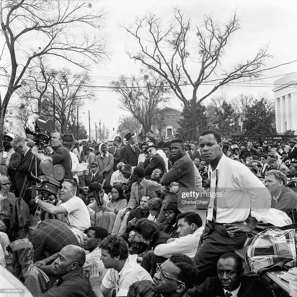 View of press, marchers, and spectators directly below the podium to listen to speakers at the end at the end of the Selma to Montgomery March, Montgomery, Alabama, March 25, 1965. American singer and Civil Rights activist Joan Baez is visible, seated at center.