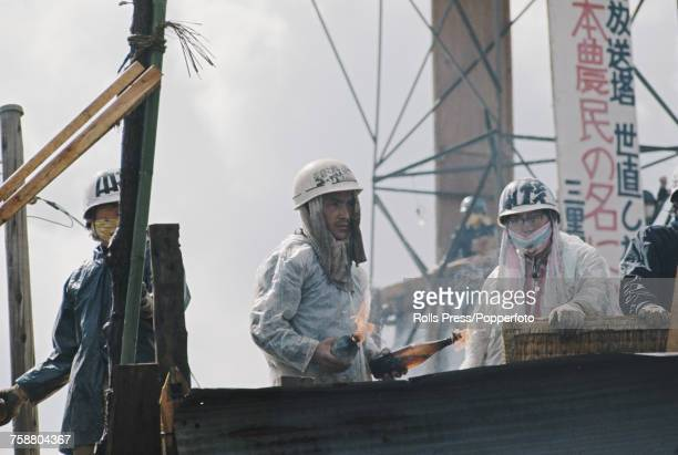 View of protesting students and farmers one holding two Molotov cocktails standing on a barricade of scaffolding poles and construction materials as...