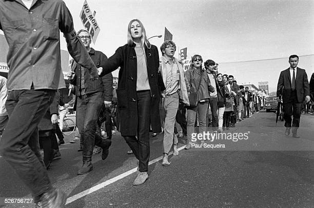 Protesters holding hands march along the road while holding signs and chanting slogans during the Vietnam Day Protest at the University of California...