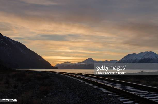 View Of Railroad Track By Lake At Sunset
