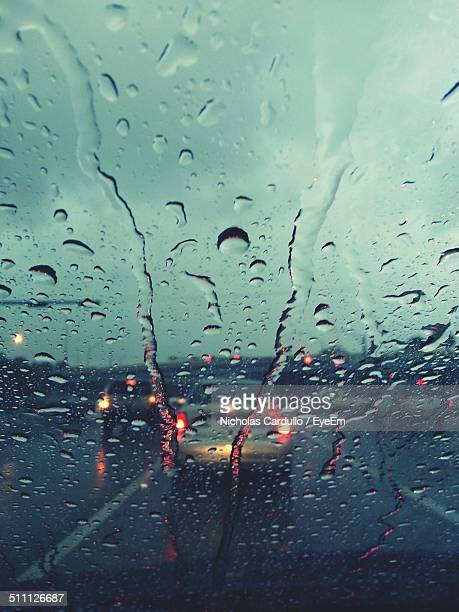 View of road through car windshield with raindrops