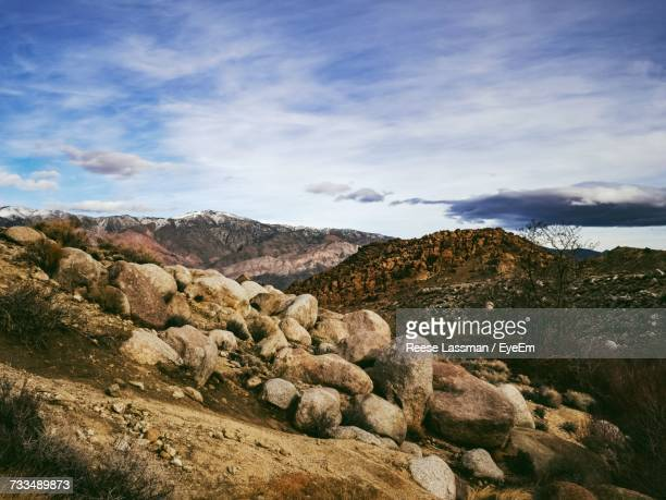View Of Rocks On Landscape Against Cloudy Sky