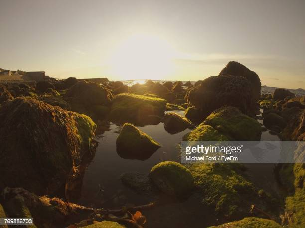 View Of Rocks On Landscape Against Sky During Sunset