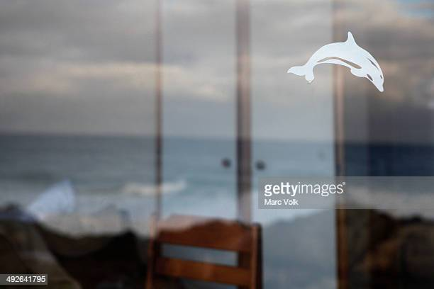 View of rough sea through window with dolphin decal on it