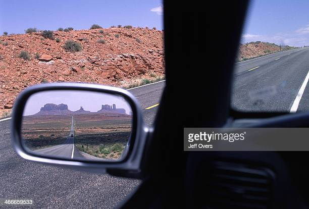 View of Route 163 towards Monument Valley in car wing mirror which straddles the borders of Arizona and Utah West America