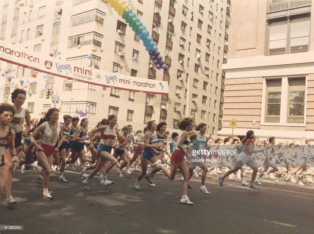 View of runners as they cross the starting line of the L'eggs Mini Marathon (later the New York Mini Marathon) at the intersectoion of Central Park West and West 63rd Street, late 1970s. The building at right is the Ethical Culture School.