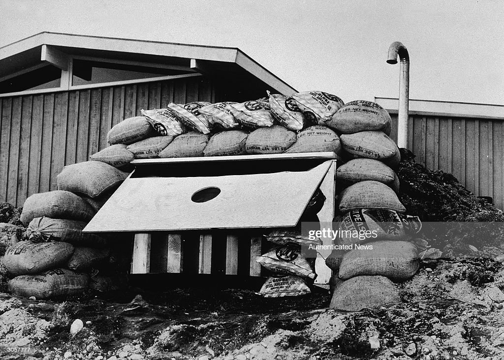 View of sandbags piled around the entrance to a family foxhole fallout shelter to provide further protection, mid twentieth century.
