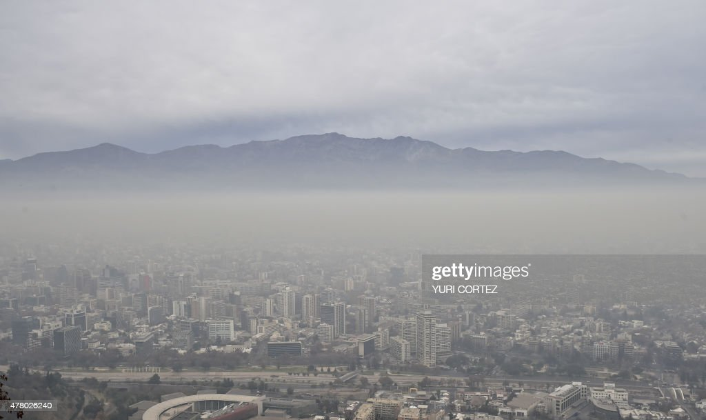View of Santiago covered by smog on June 21, 2015. Stations located in the west of the city, as Pudahuel and Cerro Navia, presented critical levels of pollution, after days with low environmental and despite contingency measures taken by the authorities. High levels of air pollution occur after several days with poor ventilation and despite three consecutive days under state environmental 'pre-emergency', a measure that paralyzes the movement of 20% of the cars and some 700 factories. AFP PHOTO/ Yuri CORTEZ /