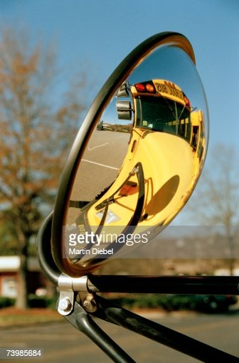 View of school bus in rear-view mirror