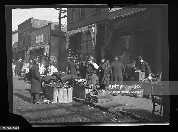 View of secondhand clothing and shoes stands on Jefferson Street in the Maxweel Street market area Chicago Illinois 1906