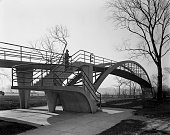 View of section of footbridge that spans over Lake Shore Drive view of archspan and staircase leading up to the bridge and a man in heavy overcoat...