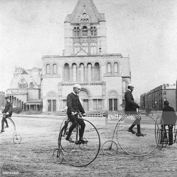 View of several man as they ride pennyfarthings on the plaza near Trinity Church New York New York 1880s