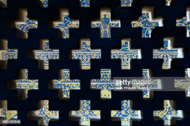 View of Sheikh Lotfollah Mosque tilework across the cross shape holes of a brick wall, Isfahan, Iran