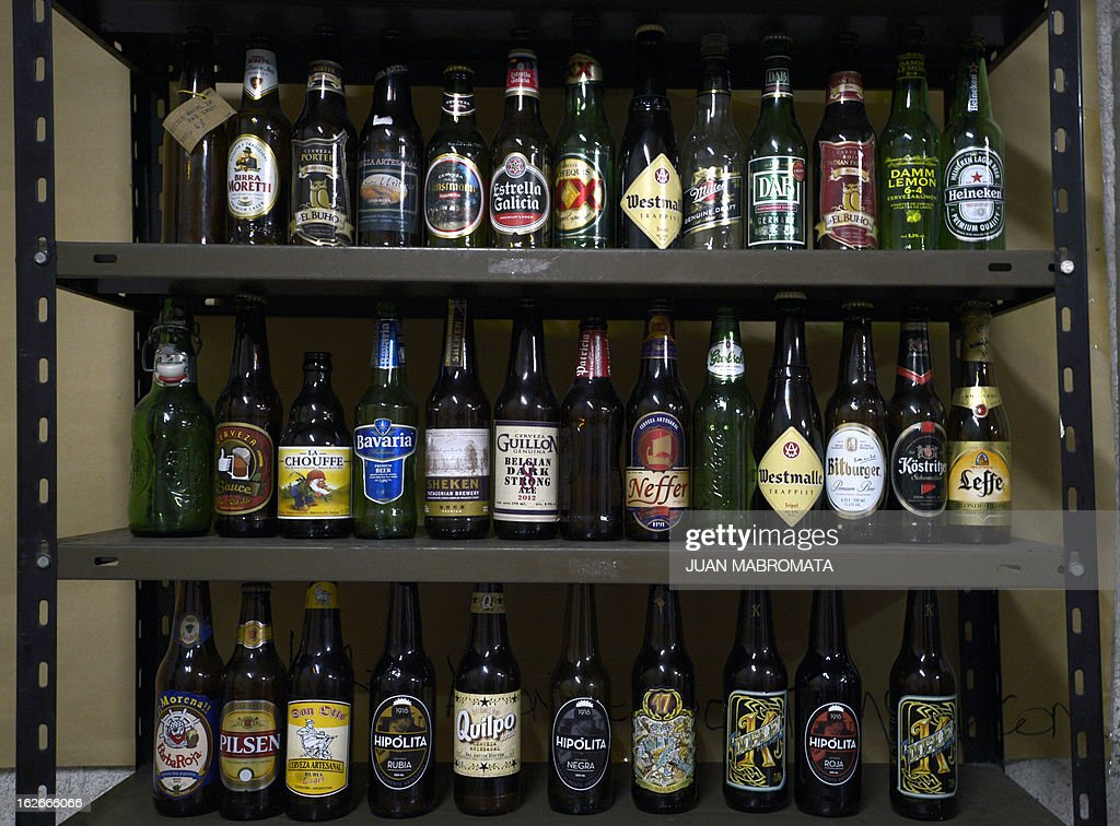 View of shelves displaying beer bottles including Argentine craft beers 'Hipolita', 'Doble K' and '17 de Octubre' (bottom shelf) in Buenos Aires on February 19, 2013. The major political parties of Argentina produce craft beers. The Peronist Party (ruling) offers a lager called 'Evita', a red beer called 'Montonera', a stout beer called '17 de Octubre' and a strong beer called 'Doble K', which can be tasted at 'Peron Peron' bar and restaurant. On the other hand, the Radical Party offers 'Hipolita' in three flavors: lager, dark and red, in the local headquarters.
