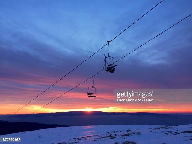 View of ski lift over snowy hill during sunset