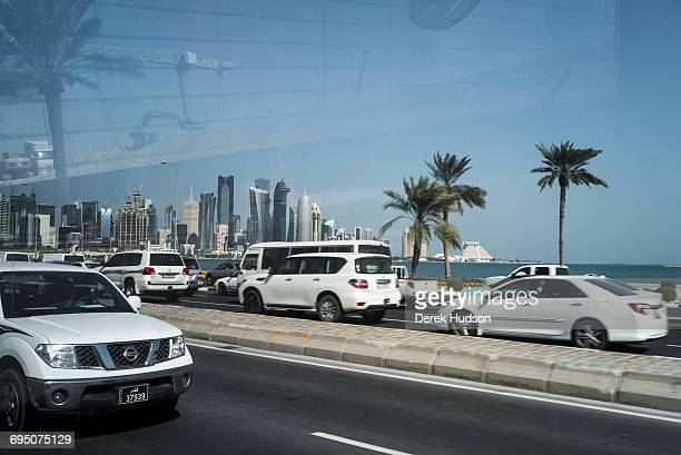View of skyscraper buildings of the city of Doha as seen from the from the back of a bus driving on the Corniche road