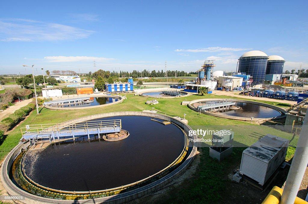 View of sludge treatment pool and storage tanks at sewage treatment plant