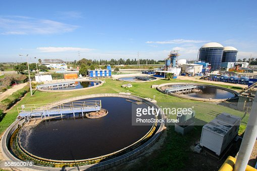 View of sludge treatment pool and storage tanks at sewage treatment plant