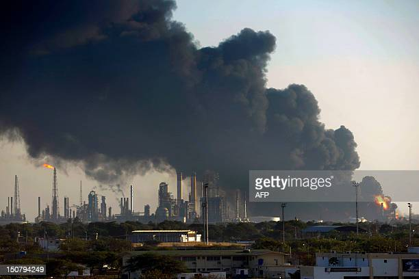 View of smoke clouds the day after an explosion in Venezuelan oil refinery Amuay part of the larger Paraguana Oil Refining Complex on August 26 in...