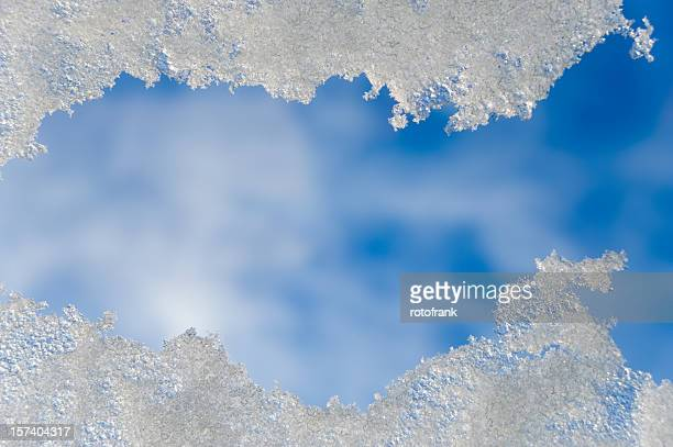 View of snow through a window or roof light and blue sky