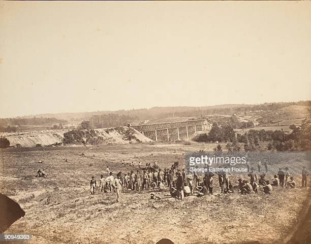 View of soldiers resting near a military bridge spanning over the Chattahoochee River near Atlanta GA 1863