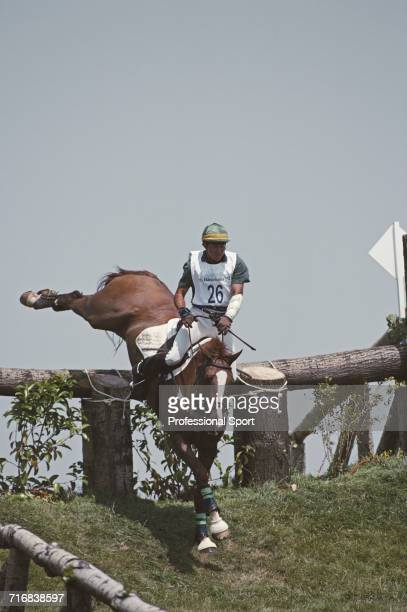 View of South African equestrian David Rissik riding Schiroubles negotiating a wooden hazard and grass slope during competition in the cross country...