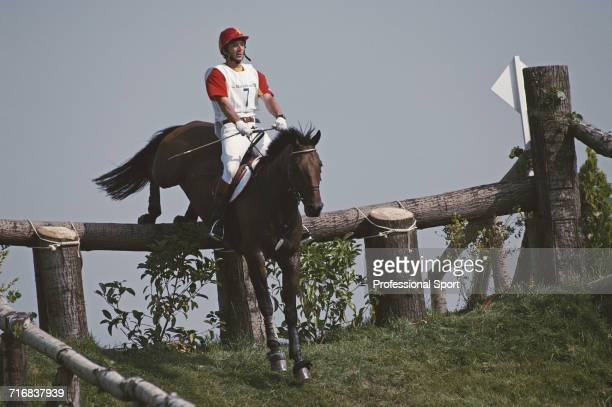 View of Spanish equestrian Luis Ivarez Cervera competitor riding Mr Chrisalis negotiating a wooden hazard and grass slope during competition in the...