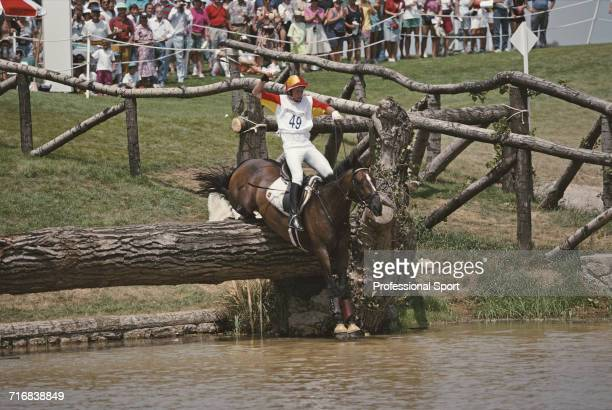 View of Spanish equestrian Santiago de la Rocha Mille riding Kinvarra negotiating a wooden log hazard in to water during competition in the cross...