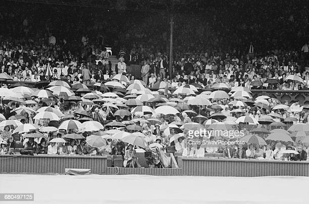 View of spectators and tennis fans holding umbrellas to shelter as rain stops play between Ivan Lendl and Boris Becker in the semi finals of the...