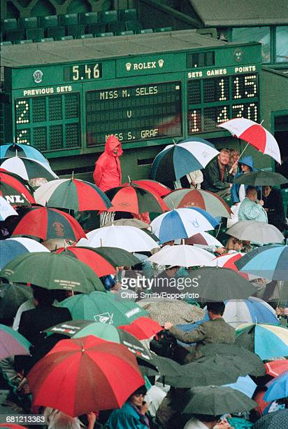 View of spectators and tennis fans holding umbrellas to shelter in front of the scoreboard as rain stops play between Steffi Graf and Monica Seles in...
