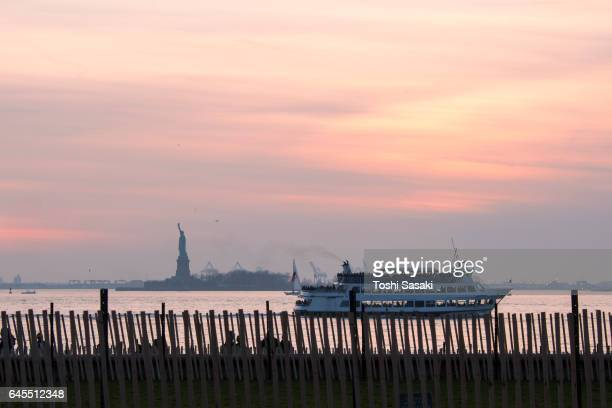 View of Statue of Liberty in the sunset glow from Battery Park City New York. A Tour Boat runs on the New York Bay.