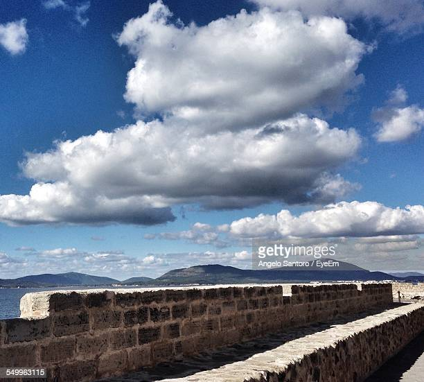 View Of Stone Wall Against Blue Sky And Clouds