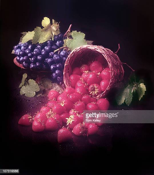 View of strawberries spilling out from a basket with a bunch of blueberries in the background against a reflective dark surface 2002