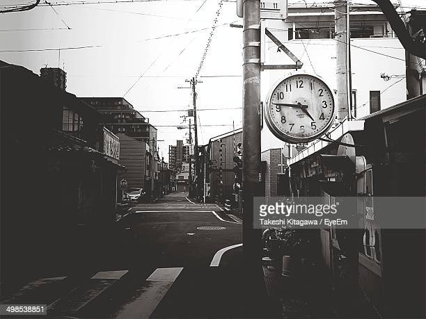 View of street with large clock mounted on pole