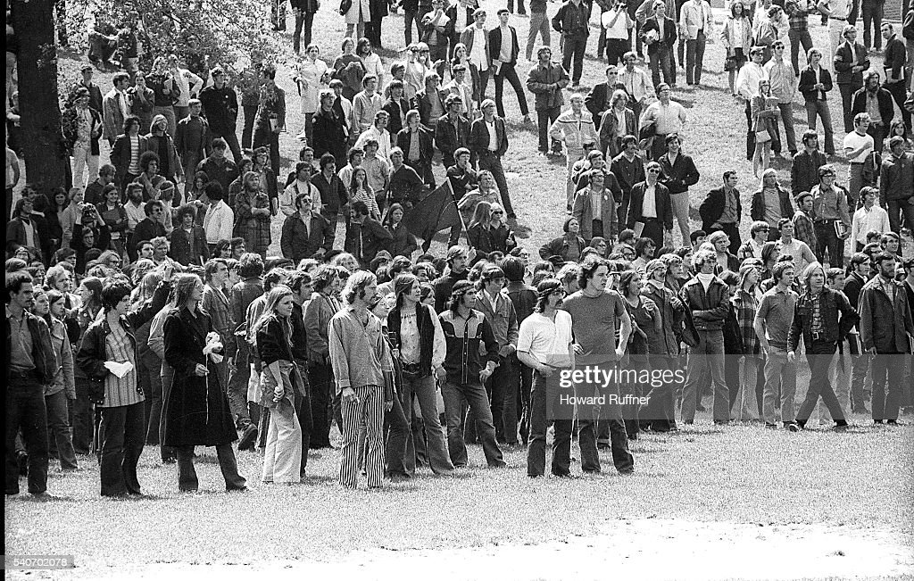 View of students, at the base of Blanket Hill, during an anti-war demonstration at Kent State University, Kent, Ohio, May 4, 1970. Shortly after this shot was taken, four students were shot and killed by guardsmen, who opened fire at some 600 demonstrators during the incident. Among the casualties was Jeffrey Miller (1950 - 1970), seen here at center, dressed in a cowboy shirt and headband, with his thumbs in his pockets. Also visible is Mary Ann Vecchio, in dark, v-neck blouse and patterned jeans (at center right, behind the man in the t-shirt at center fore); Vecchio was later photographed crying over Miller's body in the Pulitzer prize-winning photograph that came to define the event.