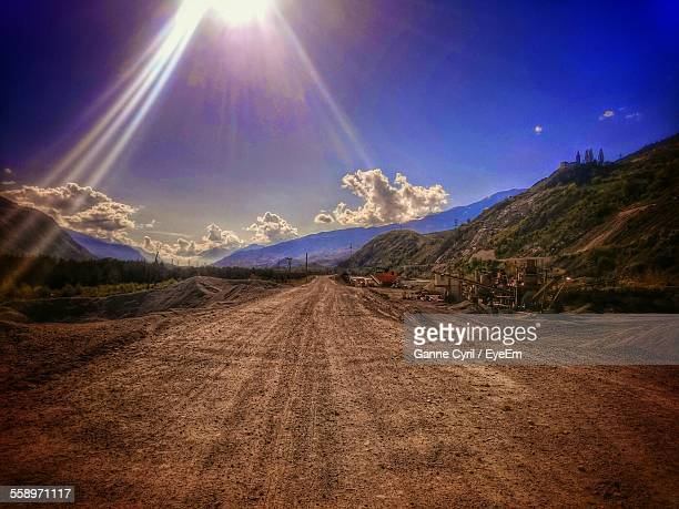 View Of Sunbeams Over Dirt Road In Mountain Landscape