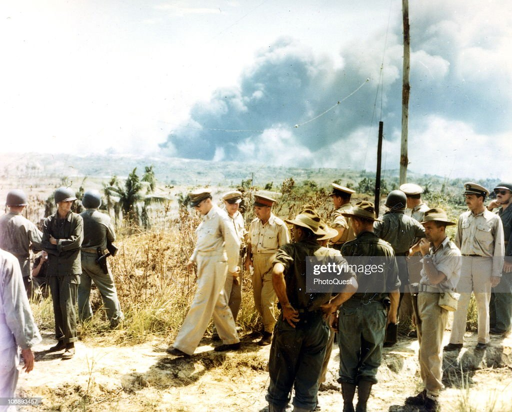View of Supreme Allied Commander American General Douglas MacArthur (1880 - 1964) (center left, walking with head down) and Australian Lieutenant General Leslie James Morshead (1889 - 1959) (center right, with red cap band), Commander of the Second Australian Army, on the the beach with Australian troops at Balikpapan, Dutch East Borneo, July 1, 1945. Among the others are Australian Air Vice Marshal William D. Bostock (1892 - 1968) and American Amphibious Forces Commander Vice Admiral Daniel E. Barbey (1889 - 1969).
