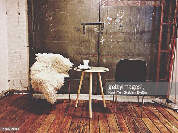View of table and chairs on wooden floor in room