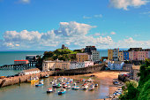 'Picturesque view of boats in Tenby Harbour, with its clusters of colourful painted houses, and Castle Hill'
