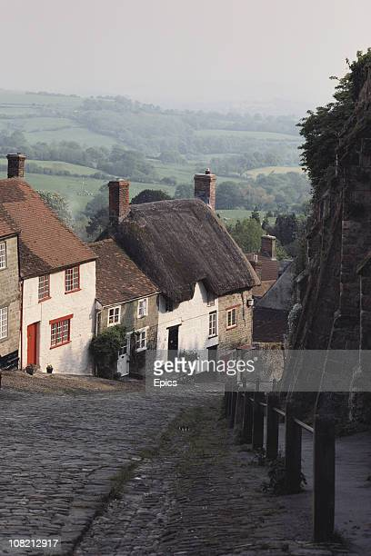 A view of thatched cottages and the cobbles of Gold Hill in Shaftesbury which runs steeply down rural Blackmoor Vale Dorset May 1984 Many of the...