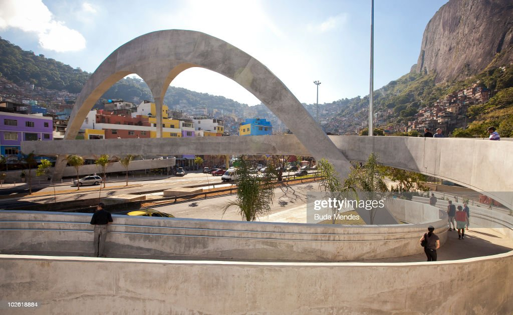 View of the arch and footbridge projected by Brazilian architect Oscar Niemeyer as part of the Rocinha Sports Complex project, located at the Lagoa-Barra driveway in Rocinha shantytown, on July 4, 2010 in Rio de Janeiro, Brazil. The footbridge, of which drawnings were donated by renowned architect Oscar Niemeyer to Rio's government, is one of the latest features of a 15000 square-meter complex built to bring sports and leisure to the 250,000 inhabitants of Rocinha, and aimed at the 2016 Summer Olympics to be held in Rio de Janeiro. With a runway almost 60 meters long, the footbridge's main feature is an arch resembling the existing arch in the Apotheosis Square, the main stage of Rio's worldwide known Samba schools annual parede.