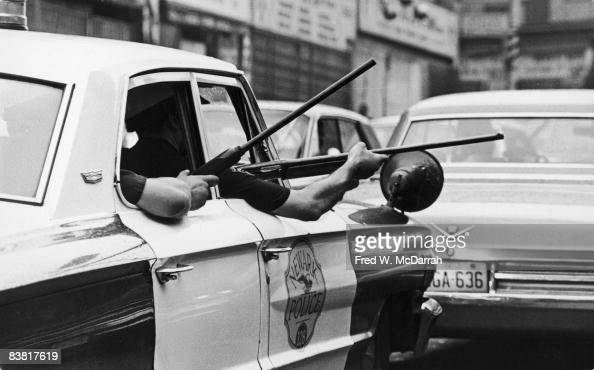 View of the arms of police officers as they hold rifles out of the windows of a police cruiser on Springfield Avenue during the Newark riots Newark...