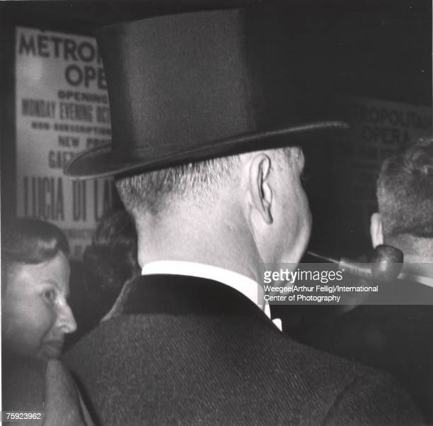 View of the back of a man who wears a top hat and smokes a pipe as he enters the Metropolitan Opera House New York New York 1940s Photo by...