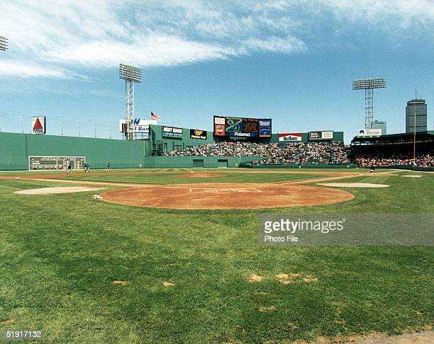 View of the baseball field the Green Monster leftfield wall and spectators in the stands from behind home plate at Fenway Park Boston Massachusetts...