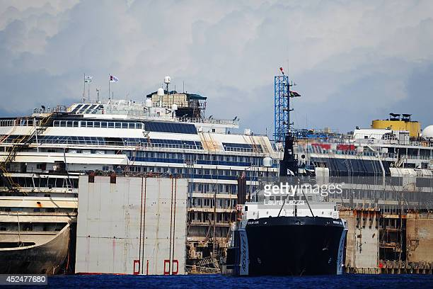 A view of the bow of the wrecked cruise ship Costa Concordia as it sits in the water with one of the tug boats stationed alongside it during the last...