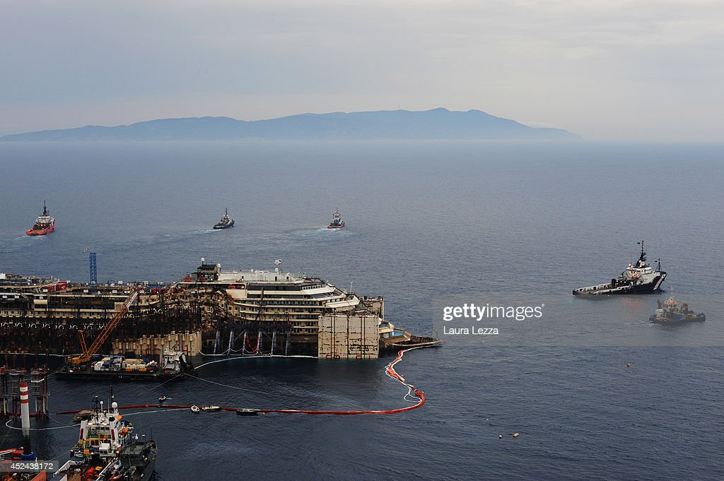 A view of the bow of the wrecked cruise ship Costa Concordia that emerges as it sits in the water during the third stage of refloating operation on July 20, 2014 in Isola del Giglio, Italy. Technicians are aiming to start towing the ship to the port of Genoa for dismantling in the next few days.