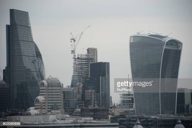 View of the City of the London's iconic buildings known as 'The Cheesegrater' and '20 Fenchurch Street' with a construction site with cranes in the...